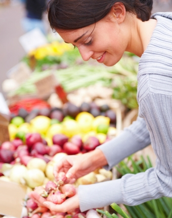 Happy young lady shopping vegetables