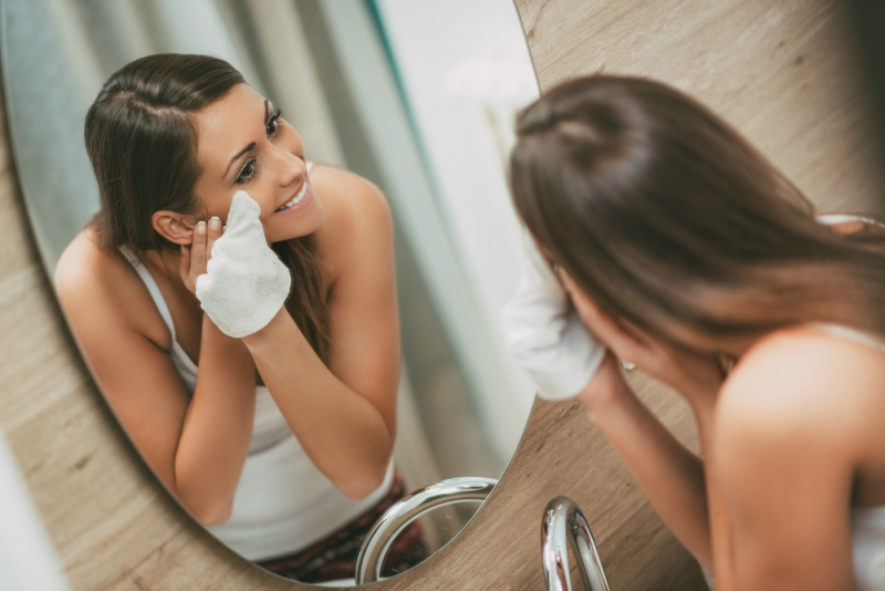 Beautiful smiling young woman removing make up in front of mirror.